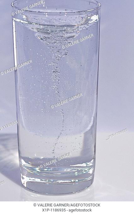 This stock image is a shot of a tall, clear, cool and refreshing glass of swirling water with lots of motion and bubbles