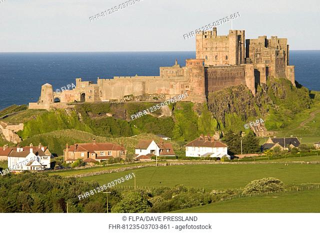 View fields and village towards castle, Bamburgh Castle, Northumberland, England, may