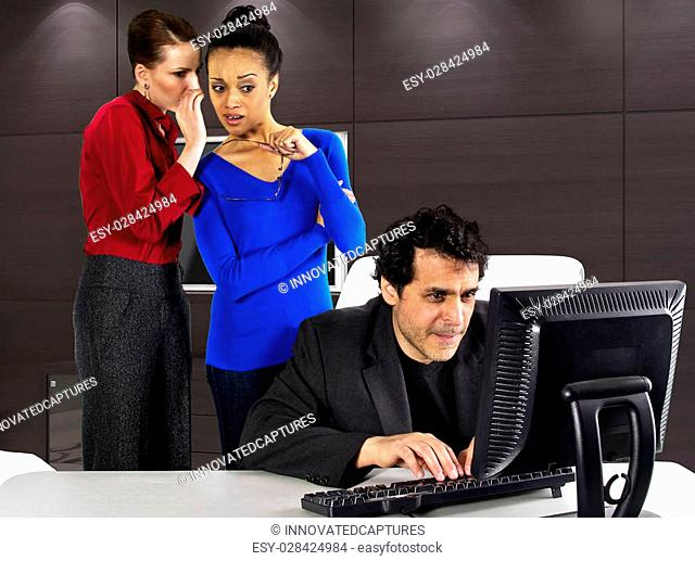 employees in an office gossiping about a male employee