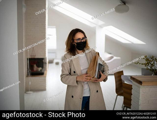 Young woman in mask coming home with purchases