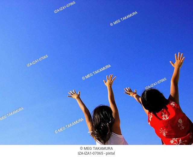 Rear view of two girls standing with their arms raised