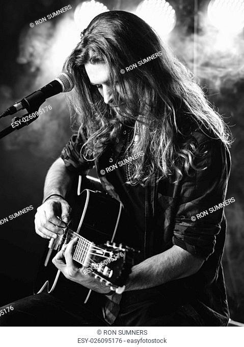 Photo of a young man with long hair and a beard singing and playing an acoustic guitar on stage with lights and concert atmosphere.