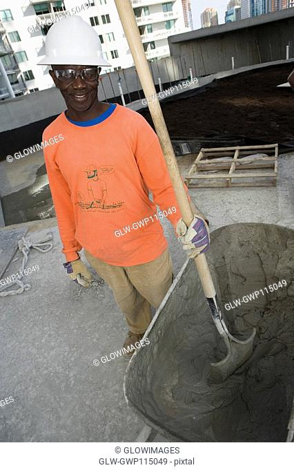 Mid adult man standing and holding a shovel