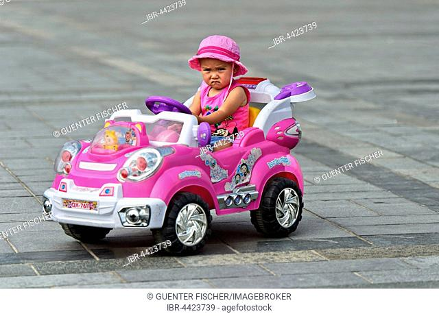 Little girl with frowning face rides in electric toy car, Genghis Khan Square, Ulaanbaatar, Mongolia