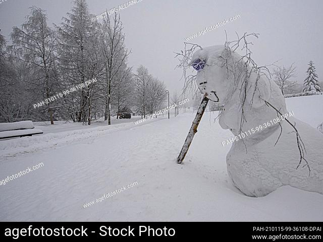 15 January 2021, Saxony, Schellerhau: A snowman stands on the side of the road in the Erzgebirge mountains, supported by a wooden pole