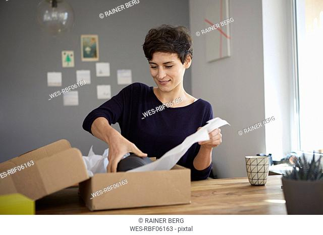 Smiling woman packing parcel at home