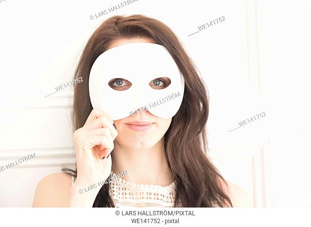Woman hiding face behind white mask. Concept of identity, mystery, and disguise