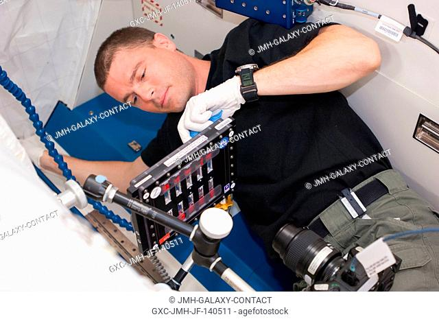 NASA astronaut Reid Wiseman, Expedition 40 flight engineer, conducts a session with the Binary Colloidal Alloy Test-C1, or BCAT-C1