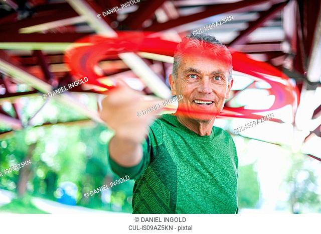 Senior man throwing flying ring under bridge