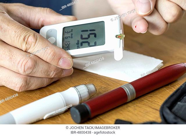 Diabetics measuring blood glucose, a drop of blood is applied to the measuring strip of the blood glucose meter, Germany