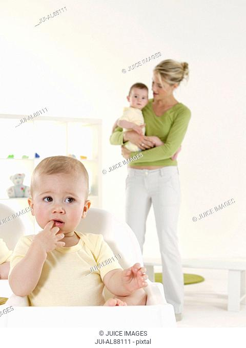 Baby in highchair with mother and sibling in background