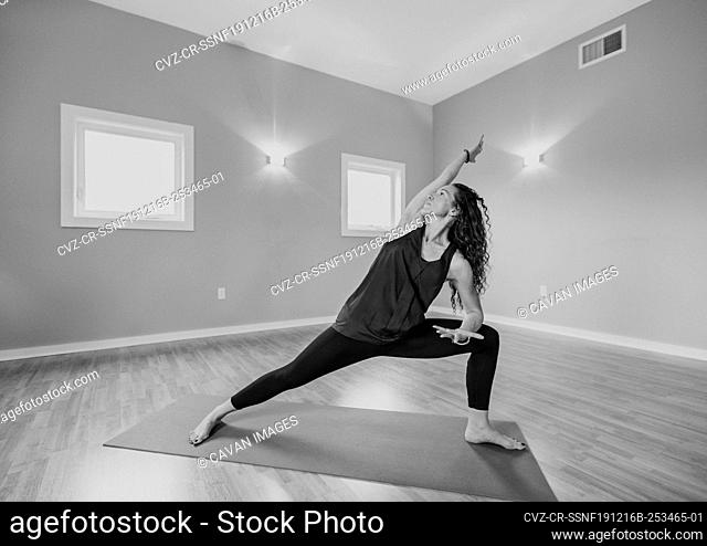 black and white image of middle age woman doing yoga in a studio