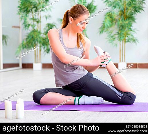 The young woman exercising in sports hall in healthy concept