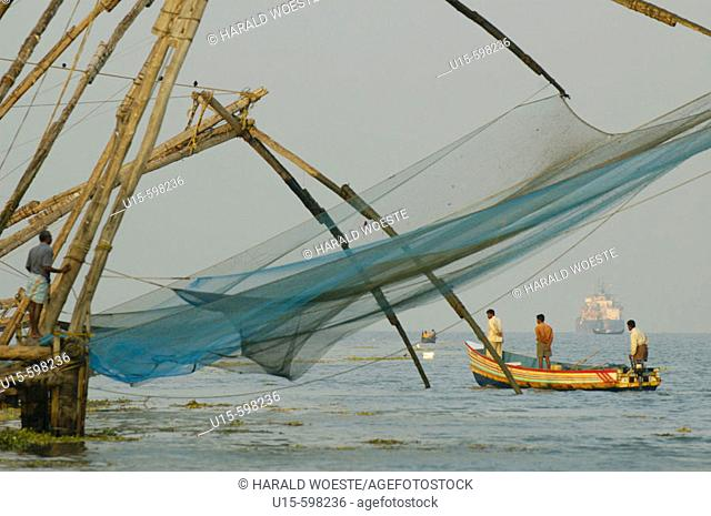 India, Kerala, Fort Cochin (Cochi, Kochi). Indian fishermen in their small boat and chinese style fishing net in Cochin harbour