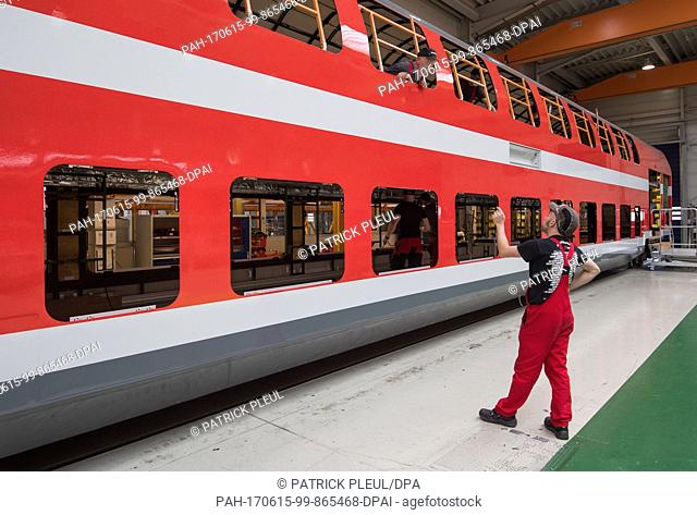 Employees work on a double-decker train car at the production hall of the company Bombardier Transportation in Bautzen, Germany, 15 June 2017