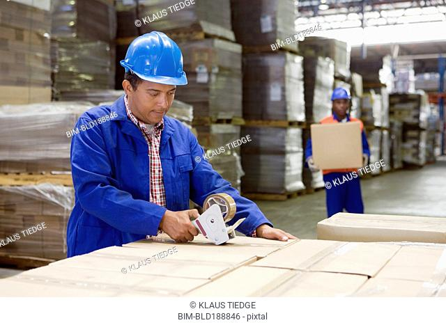 African worker taping boxes in warehouse