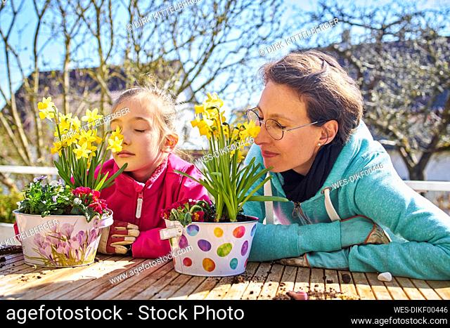 Mother and daughter smelling flowers on balcony
