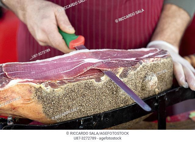 Italy, Umbria, Norcia, Stall Market, Market Stall Trader Carving a Ham. . .