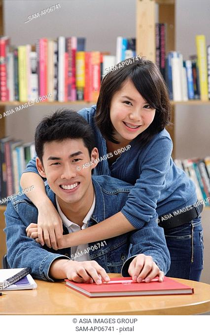 Couple in library, woman embracing man from behind