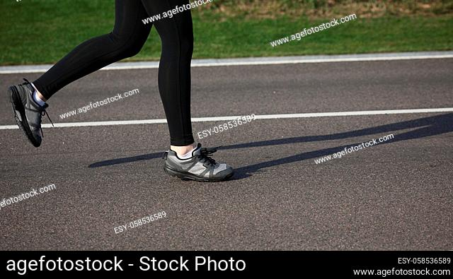 Shallow depth of field, toned with instagram like filter, flare effect. Closeup of female in running shoes going for run on road at sunrise or sunset