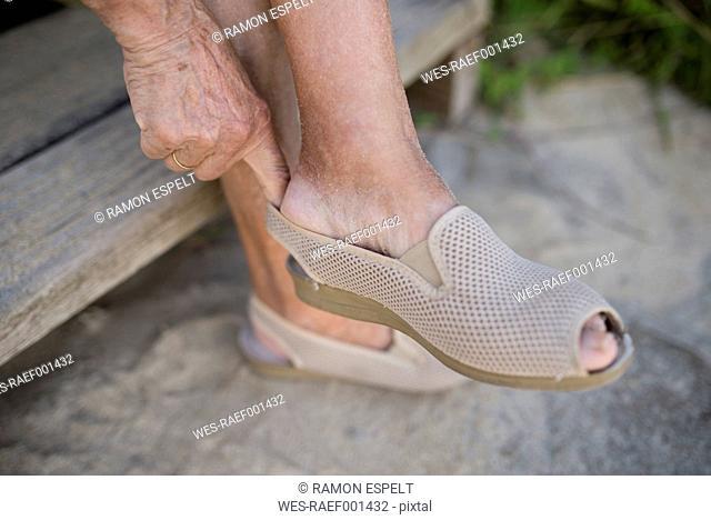 Senior woman putting on shoe