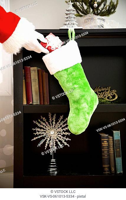 Santa Claus putting gift into Christmas stocking