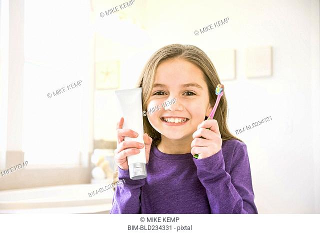 Smiling Caucasian girl holding toothbrush and toothpaste tube in bathroom