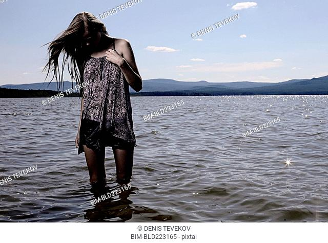 Woman wading in remote lake