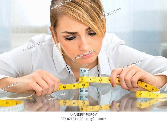 Portrait Of Businesswoman Holding Measuring Tape Around Dollar Banknote