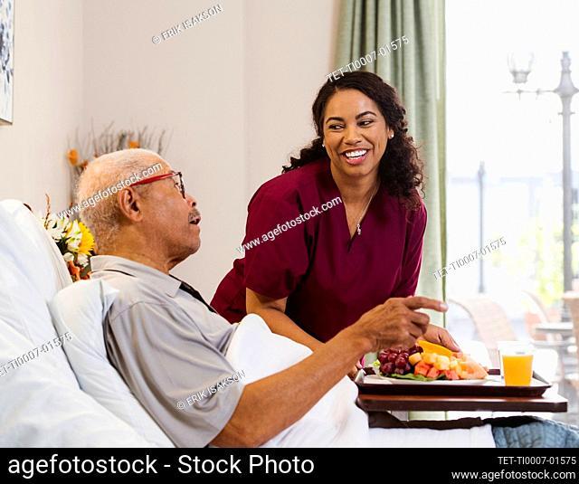 Nurse bringing healthy meal to senior man in bed