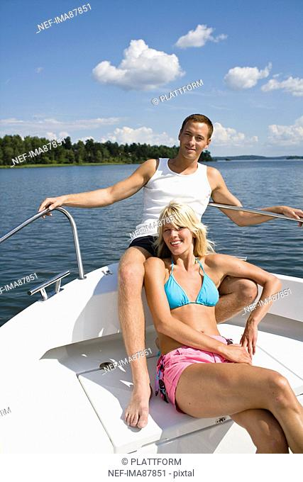 Young couple relaxing in yacht on lake