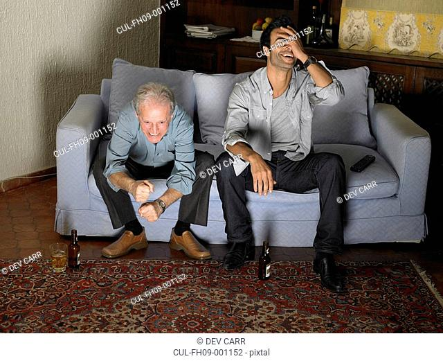 Senior father and son sitting on sofa watching television