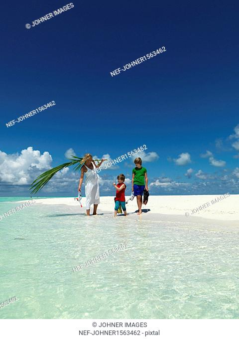 Mother walking with sons on sandy beach