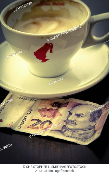 A lone coffee cup and saucer with a 20 kuna banknote on the table in Croatia