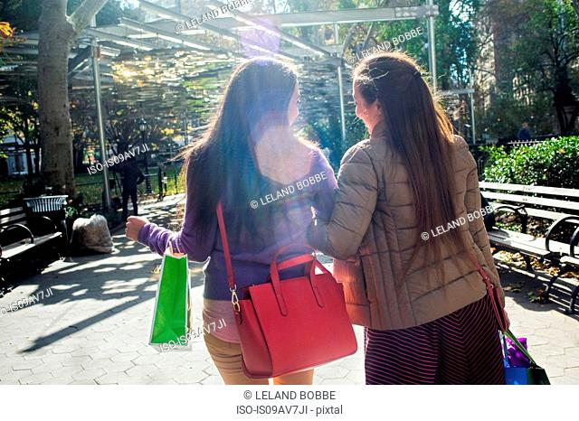 Rear view of young female adult twins strolling in park with shopping bags
