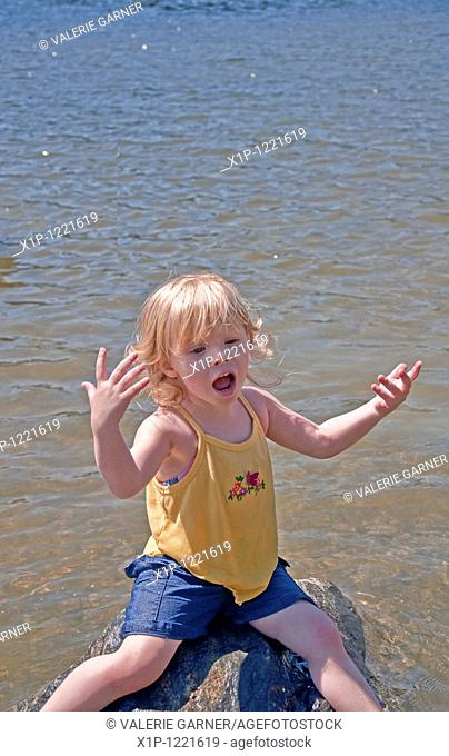 his young Caucasian girl is thoroughly enjoying a summer moment as she's sitting on a rock in a lake and singing her little heart out