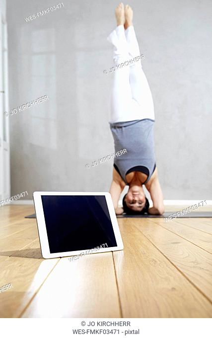 Woman practising yoga doing a headstand behind tablet