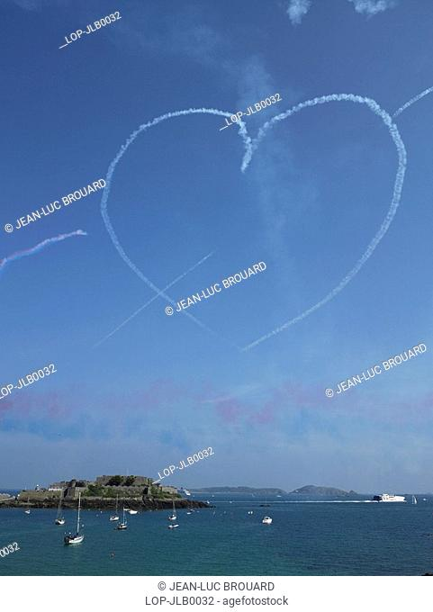 England, Channel Islands, Guernsey, A heart made of smoke hangs in a blue sky over Castle Cornet in Guernsey after a Red Arrows display