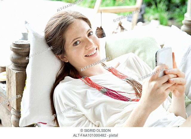 Young woman lying on back with smartphone in hands, portrait