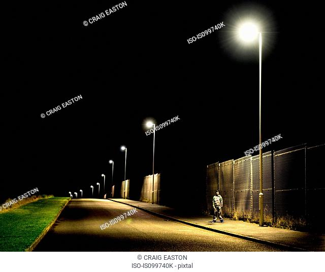 Boy standing on pavement at night with street lights