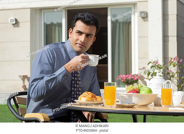 India, Businessman having breakfast in garden