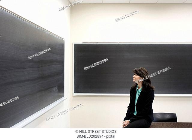 Caucasian teacher sitting in empty classroom