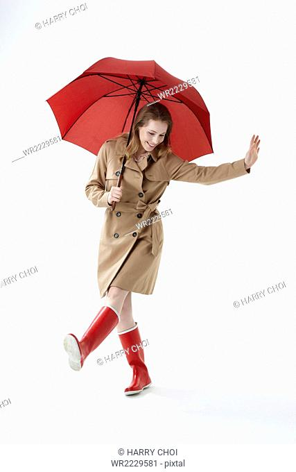 Young smiling woman wearing red umbrella, trenchcoat and red boots kicking looking down