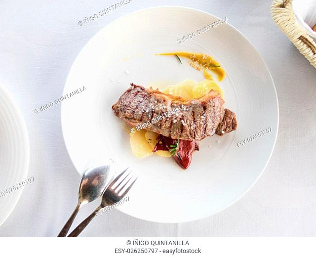 aerial view elegant white circular plate with grilled veal steak with salt flakes over flat potatoes red pepper rosemary and spoon and fork on white tablecloth...