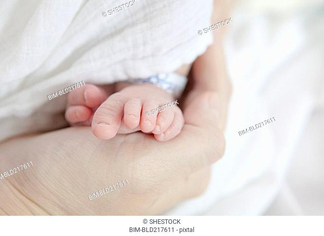 Caucasian mother holding foot of newborn daughter
