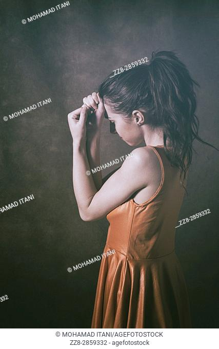 Scared young woman hiding face with hands
