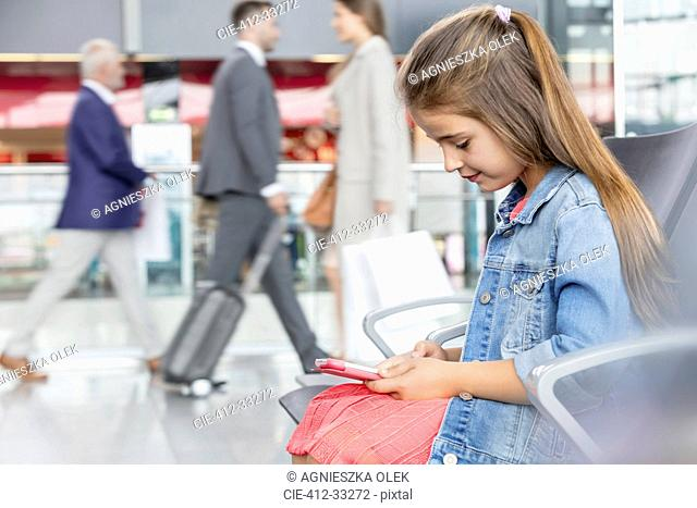 Girl using digital tablet in airport departure area