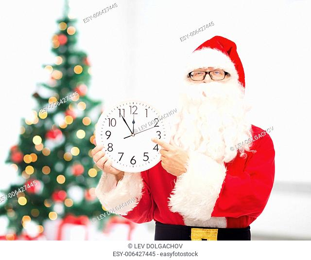 christmas, holidays and people concept - man in costume of santa claus with clock showing twelve pointing finger over living room with tree background