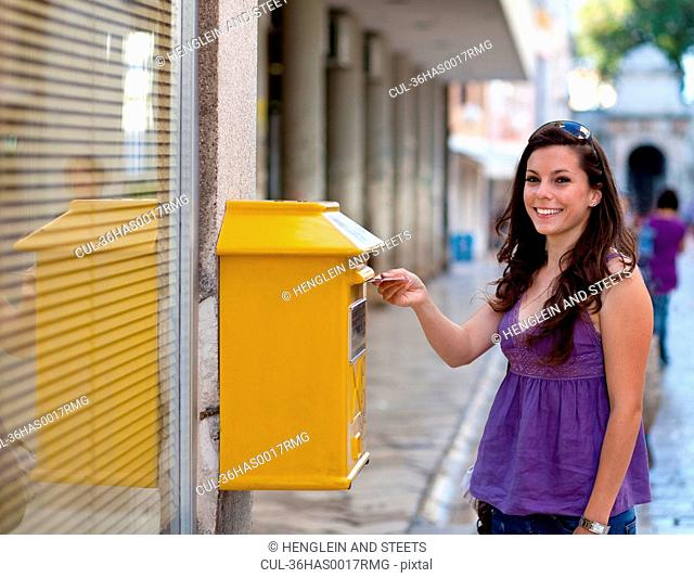 Woman putting postcard in mailbox
