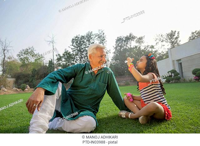 India, Young girl (6-7) blowing bubbles with grandfather sitting on backyard
